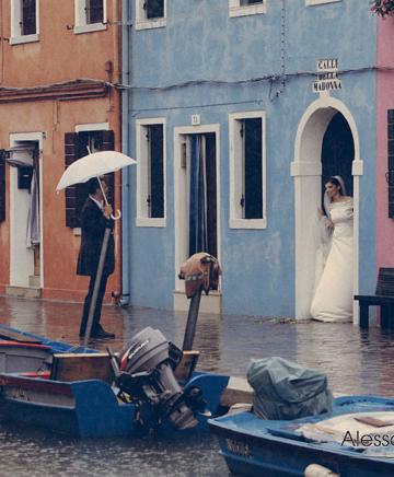 la coppia di sposi si ripara dalla pioggia sotto un portego a Burano