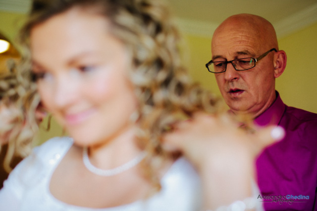 groom helps bride to get ready