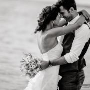 sposi si abbracciano teneramente sulla spiaggia vicino al mare