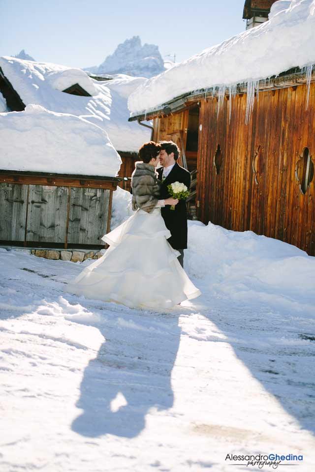 coppia di sposi si abbraccia nella neve