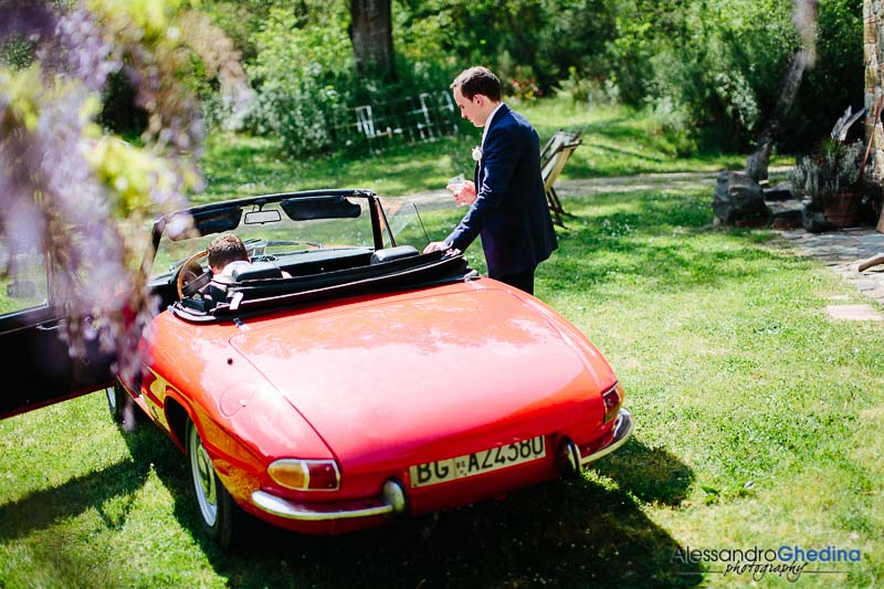 groom heading to the ceremony with a red oldtimer alfa romeo duetto
